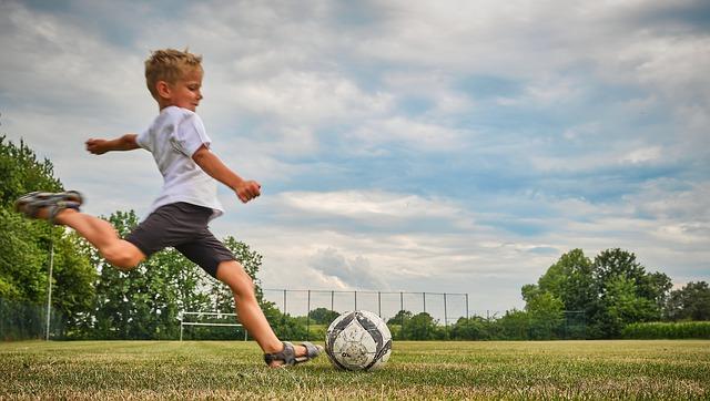 Chlapec kopající do míče na fotbalovém hřišti